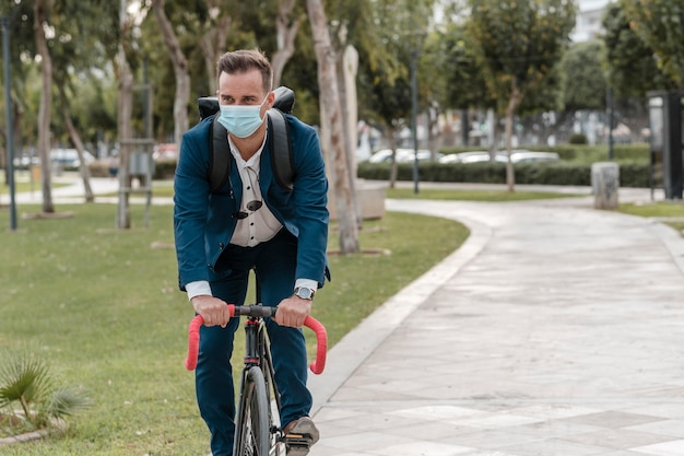 Man riding a bike while wearing a medical mask