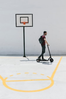 Man riding e-scooter on a basketball court