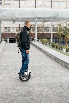 Man riding fast on electric unicycle on city street.