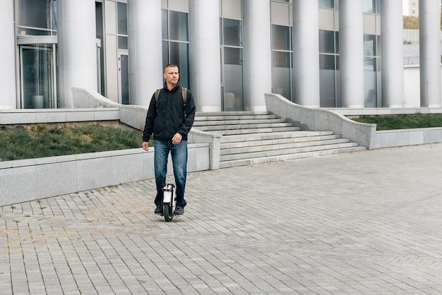 街の通りで電動一輪車に高速で乗っている男。移動式の携帯型個人輸送車両。働くために速く(euc)に乗っている電気モノホイールの男