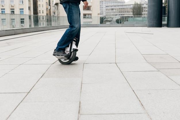 街の通りで電動一輪車に高速で乗っている男。移動式の携帯型個人輸送車両。働くために速く(euc)に乗っている電気モノホイールの男 Premium写真