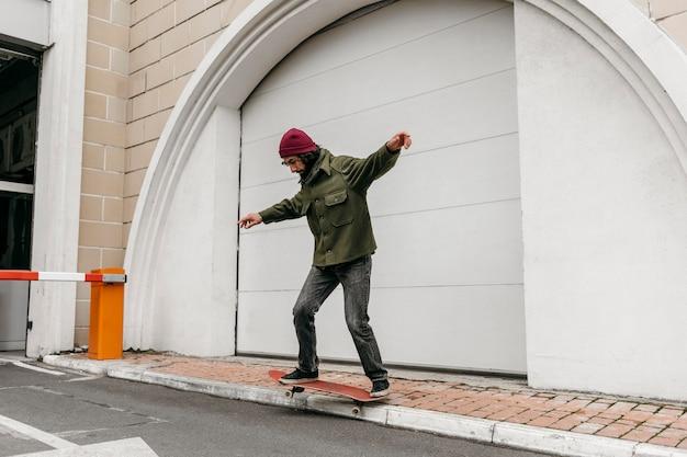 Uomo che cavalca il suo skateboard all'aperto in città