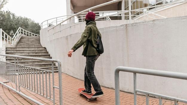 Uomo che cavalca il suo skateboard fuori in città