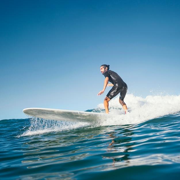 Uomo che cavalca la sua tavola da surf