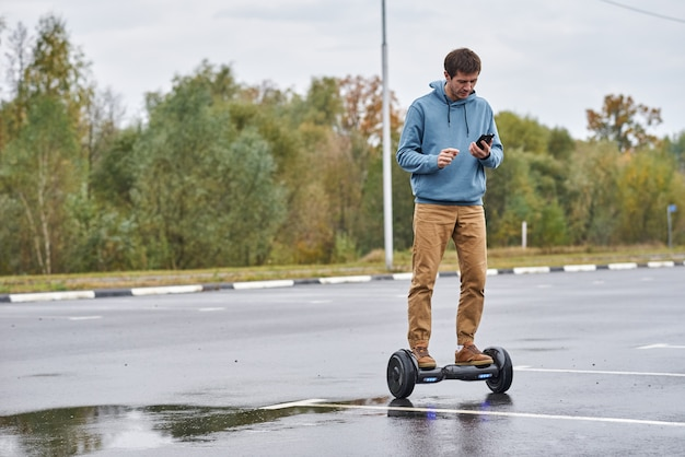 Man riding on the hoverboard and using smartphone outdoor