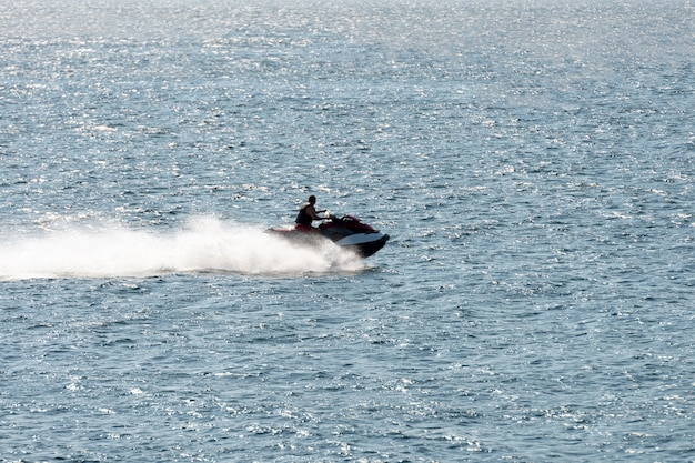 Man riding a jet ski shooting in backlit by sunset
