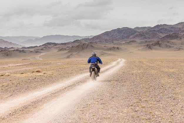 Man riding a motorbike in the steppes of mongolia, on the hills of mongolia
