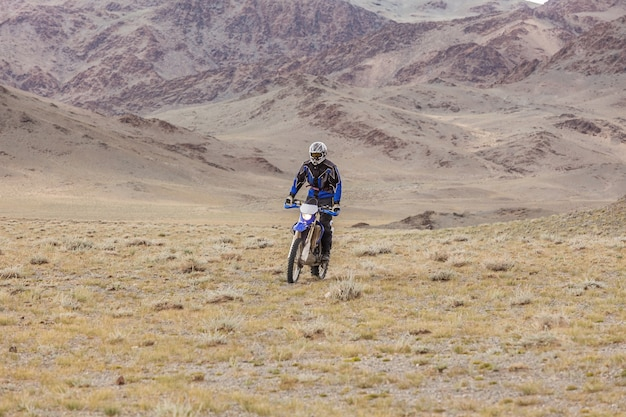 Man riding a motorbike in the steppes of mongolia, on the hills of mongolia Premium Photo