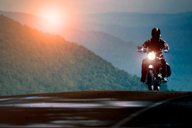 山の高速道路でバイクに乗る男