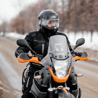 Uomo in sella a moto il giorno d'inverno