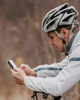 Man riding a mountain bike and checking his phone