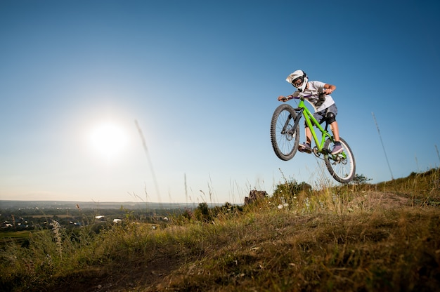Man riding a mountain bike and jumping from the hill