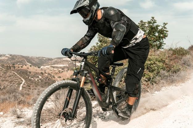 Uomo che guida una mountain bike all'aperto