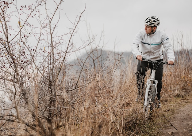 Man riding a mountain bike in special equipment with copy space