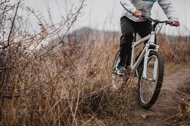 Uomo che guida una mountain bike in attrezzature speciali con copia spazio
