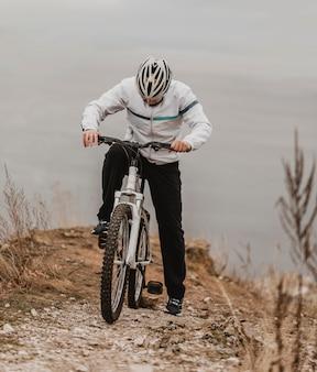 Uomo che guida una mountain bike in attrezzatura speciale