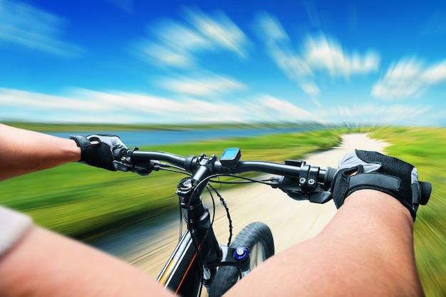 Человек, едущий на велосипеде на лугу, размытость изображения