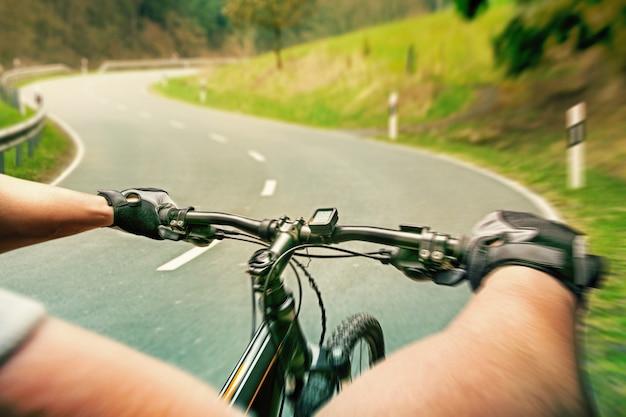 Человек, едущий на велосипеде по шоссе