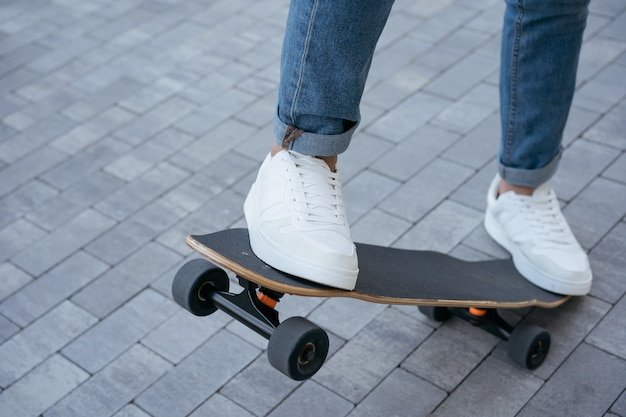 Человек катается на скейтборде на улице, практикует трюк на скейтборде