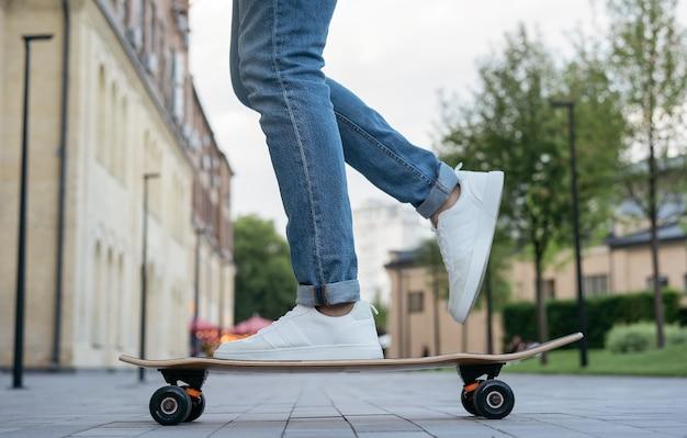 Человек катается на скейтборде по городской улице