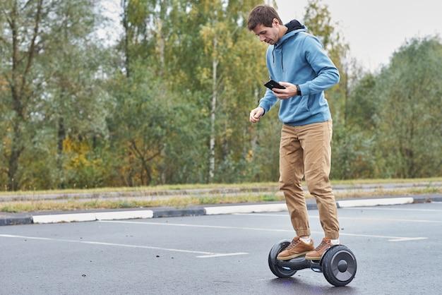 Человек, едущий на ховерборде и использующий смартфон
