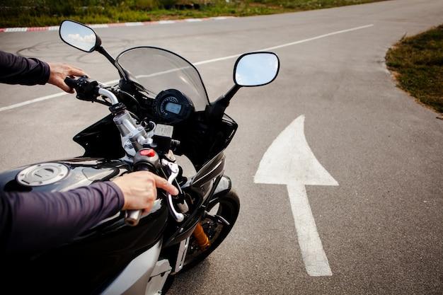 バイクの道に乗って男 Premium写真