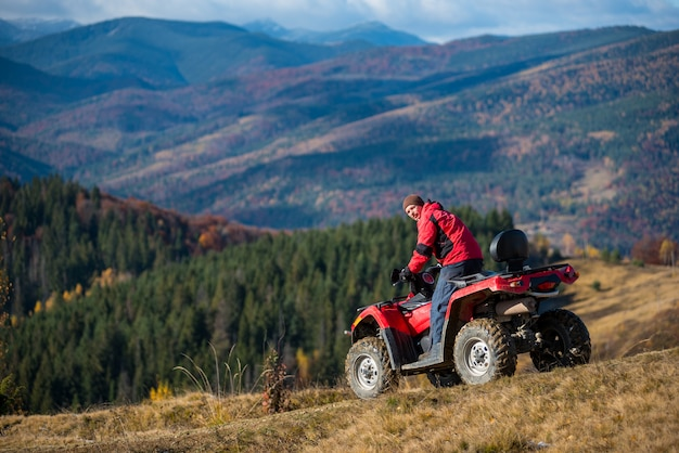 Man riding on red quad bike, looking to the camera at autumn sunny day. landscape of mountains, forest and blue sky. the concept of an active holiday in the mountains