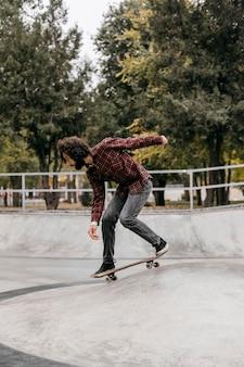 Uomo che cavalca lo skateboard all'aperto