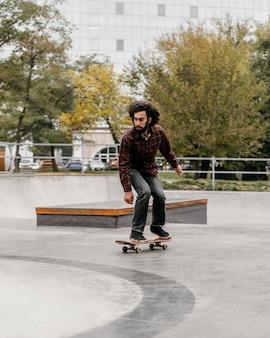 Uomo che cavalca lo skateboard fuori nel parco