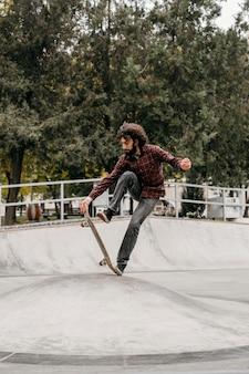 Uomo che cavalca skateboard all'esterno