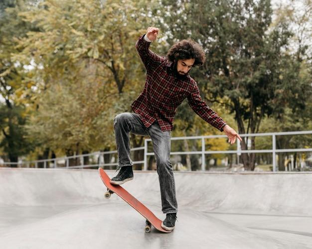 Uomo che guida lo skateboard nel parco