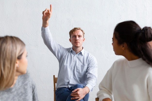 集団療法のセッションで質問のために手を上げる男