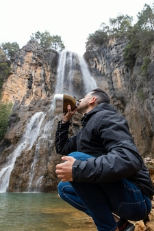Man at river drinking water