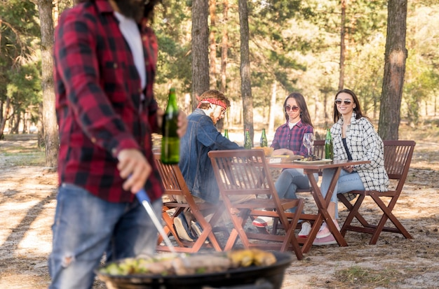 Man roasting corn on barbecue while friends converse at table outdoors
