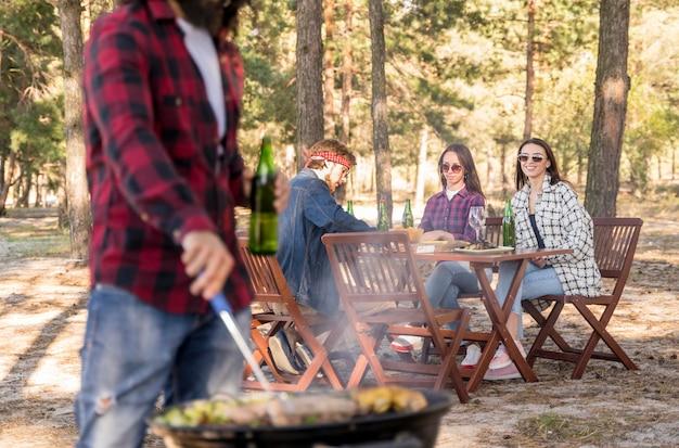 友人が屋外のテーブルで会話しながらバーベキューでトウモロコシを焼く男