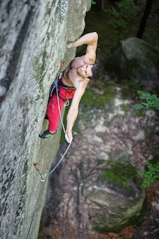 Man rock-climbing on boulders with rope engaged.