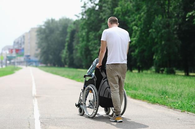 男は通りを女の子と一緒に車椅子を転がします。