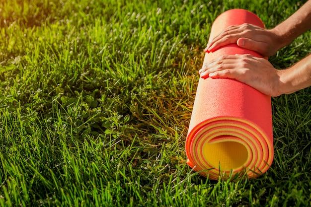 男は夏の公園の芝生の上でヨガマットをロールバックします。スポーツ用品