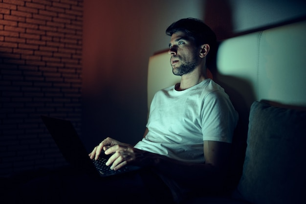 Man in the room at night watching movies rest