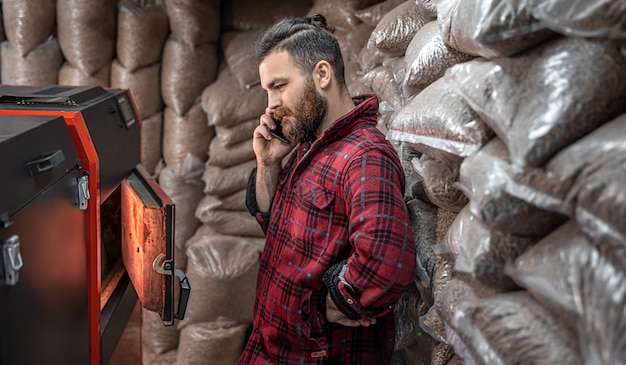 A man in a room with a solid fuel boiler, working on biofuel, economical heating.
