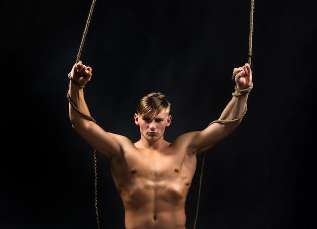 남자 로프. 보디 빌더를위한 스포츠 운동. 밧줄에 근육질 몸매를 가진 남자. 섹시한 남자는 체조를합니다.