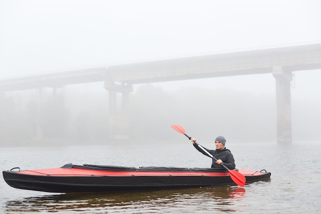 Man rowing in boat on foggy morning, holding paddle in hands, posing in water