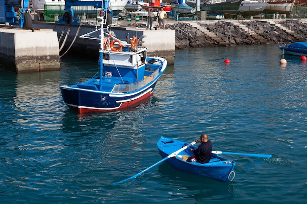 Man rowing a fishing boat to side of harbour in tenerife