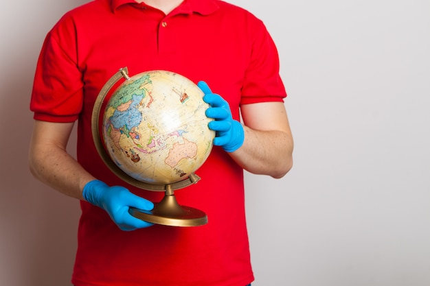 Man in rubber medical gloves holds a globe in his hands.