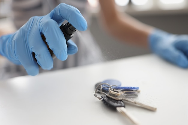 Man in rubber protective gloves puffing spray with antiseptic on bunch of keys closeup. preventive measures to combat coronavirus infection concept