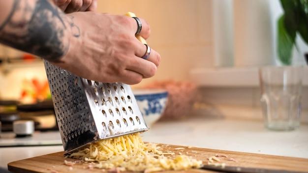 おろし金でチーズをこする男