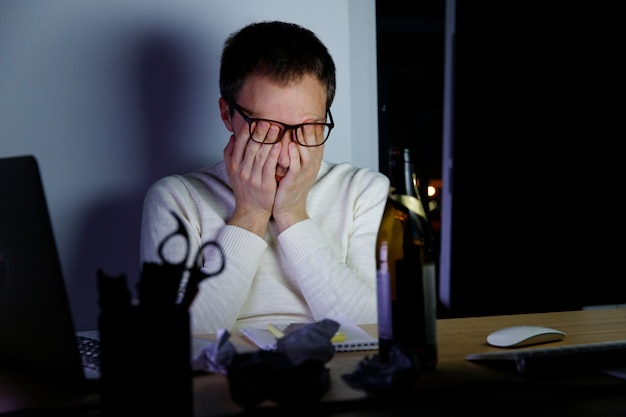 Man rubbing his tired eyes working late at night, drank a beer to relax, falls asleep from fatigue.