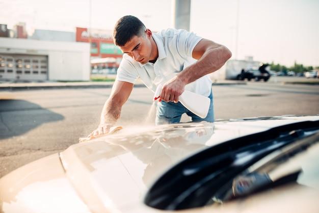 Мужчина натирает автомобиль автомобильным полиролью