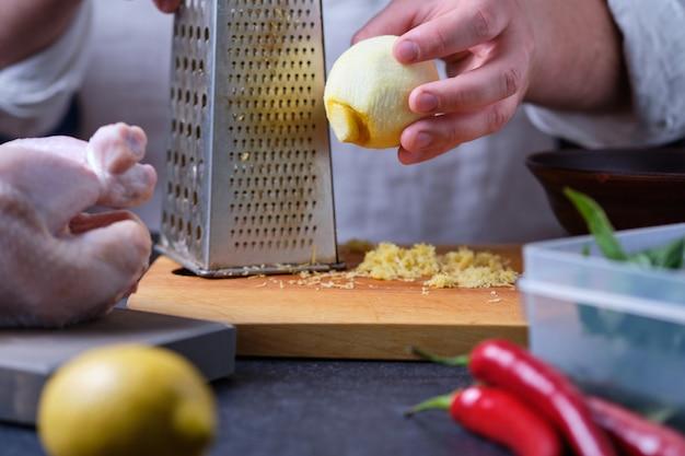 男はレモンの皮をこすります。オーブンでハーブ、スパイス、レモンを使って鶏肉を調理するプロセス