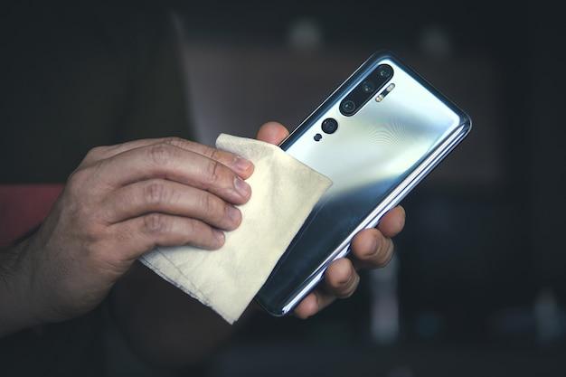 Мужчина протирает тряпкой экран своего черного смартфона. профилактика коронавируса и вирусных заболеваний. очистка мобильного телефона от пыли.
